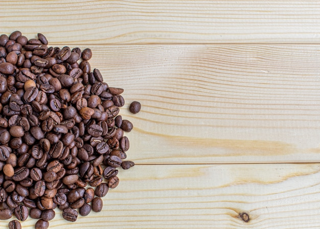 Lots of coffee beans on a wooden background. there is a place for insertion.