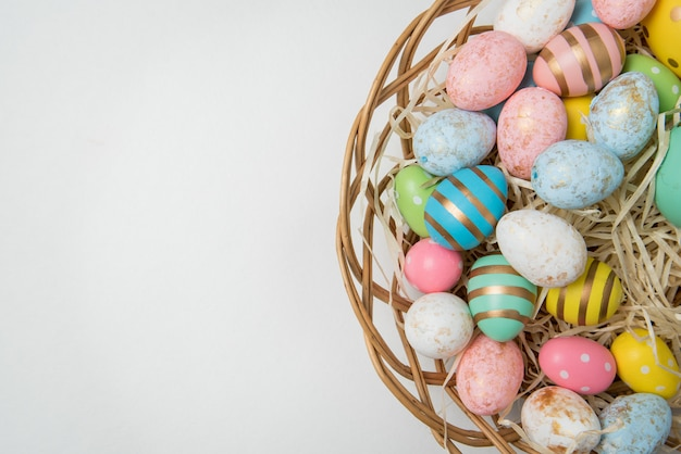 Lots of colorful easter eggs in basket. white background. happy easter. copy space