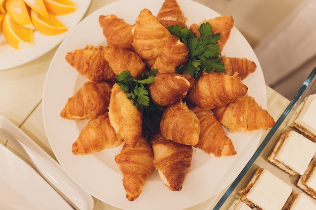 Lots of fresh croissants on a white plate on the buffet in the restaurant.