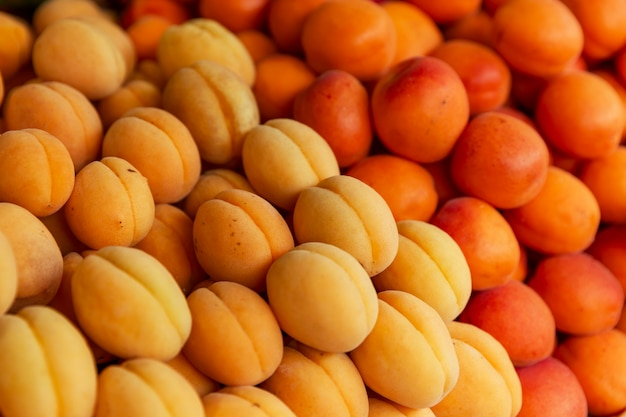 Lots of fresh juicy apricots on the market counter. vitamins, healthy eating and veganism. close-up. background.