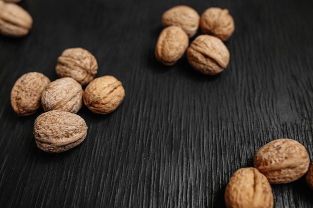 Lots of fresh nuts on a black wooden background. best practices for designer. a beautiful design from the nuts