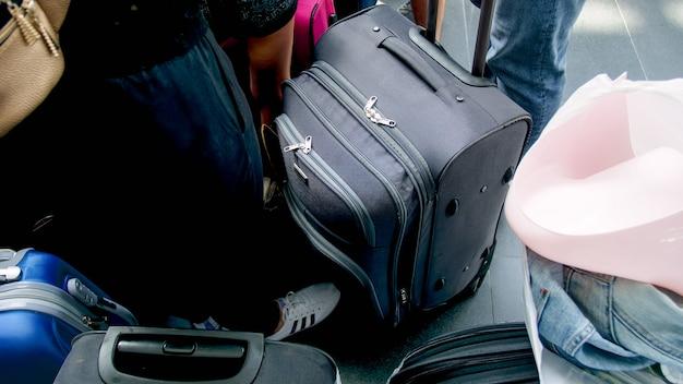 搭乗口の近代的な空港ターミナルにはたくさんのバッグやスーツケースがあります。