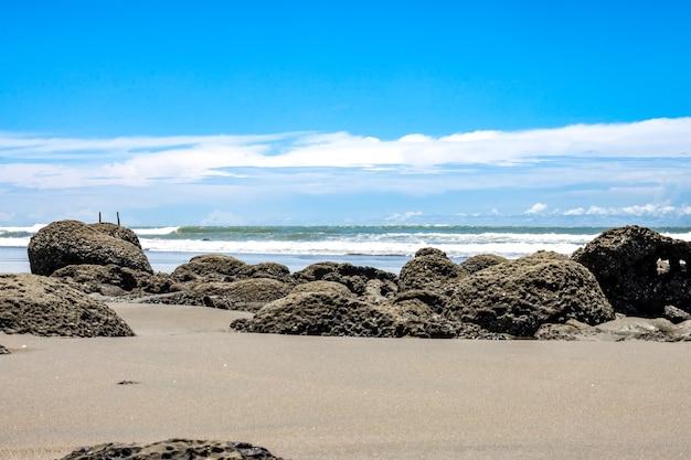 밝은 푸른 하늘 아래 바다 해변에 많은 큰 바위