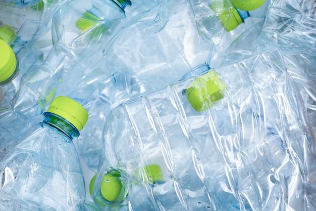 緑のキャップの背景を持つ青いプラスチックボトルがたくさん