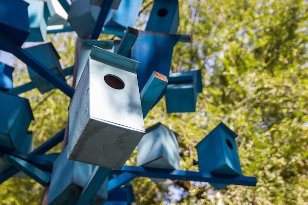 Много синих деревянных скворечников на дереве. концепция кондоминиума.