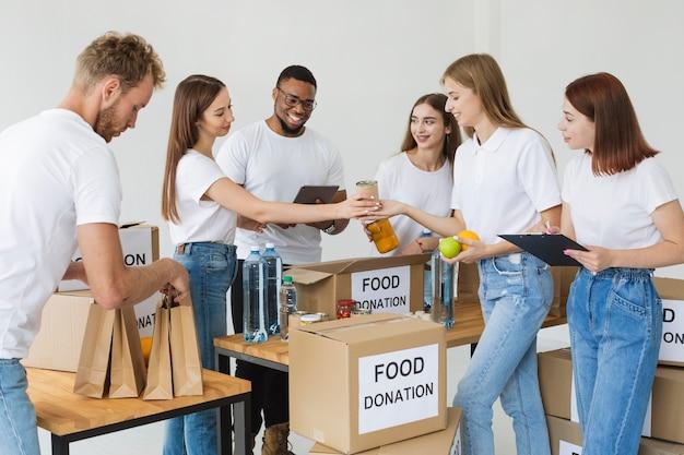 Множество веселых волонтеров готовят коробки с пожертвованиями еды