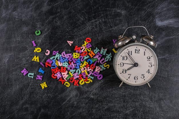 たくさんの色付きの文字、チョークボードの背景にレトロな目覚まし時計。学校に戻る。上面図。