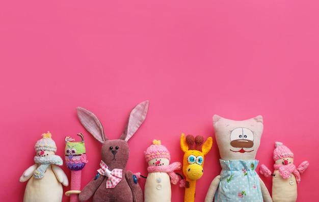많은 다채로운 어린이 장난감이 분홍색 배경 평면도에 배치되었습니다. 텍스트를위한 공간