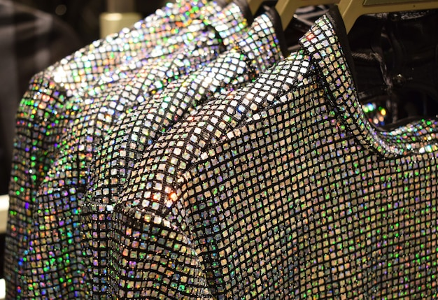 Множество разноцветных радужных пайеток на платьях на вешалках в магазине модная праздничная одежда на новый год и рождество
