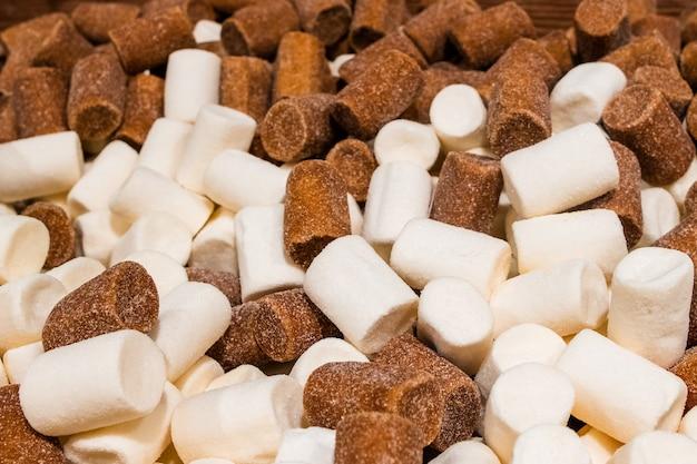 白と茶色の砂糖をトッピングした円筒形のグミがたくさん