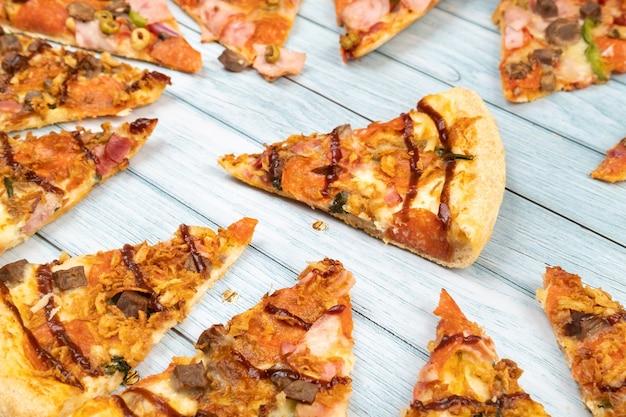 푸른 나무 배경에 맛있는 삼각형 피자 조각이 많이 있습니다.