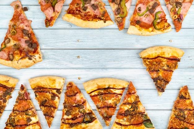 푸른 나무 배경에 맛있는 삼각형 피자 조각 많이.
