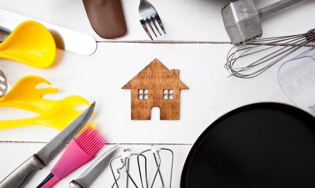 Много разных кухонных принадлежностей на деревянном столе и маленький деревянный дом между ними