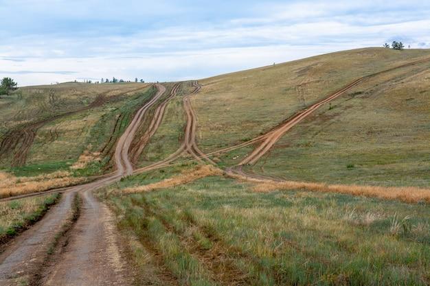 Много грунтовых дорог в степных холмах. горизонтальное изображение.