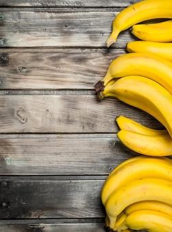 Много свежих ароматных бананов. на черной деревянной поверхности.
