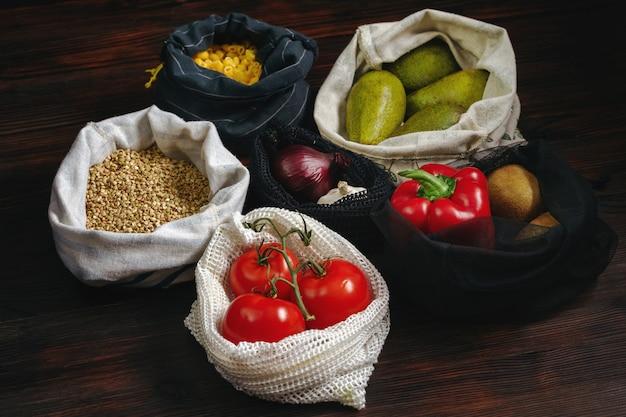 나무 테이블에 플라스틱 무료 및 재사용 가능한 가방에 많은 신선한 음식. 제로 폐기물 생활 개념.