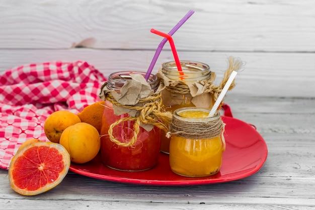 Много свежих фруктов, нарезанных на красивом деревянном фоне, свежий фруктовый напиток, джем, вкусная, здоровая еда
