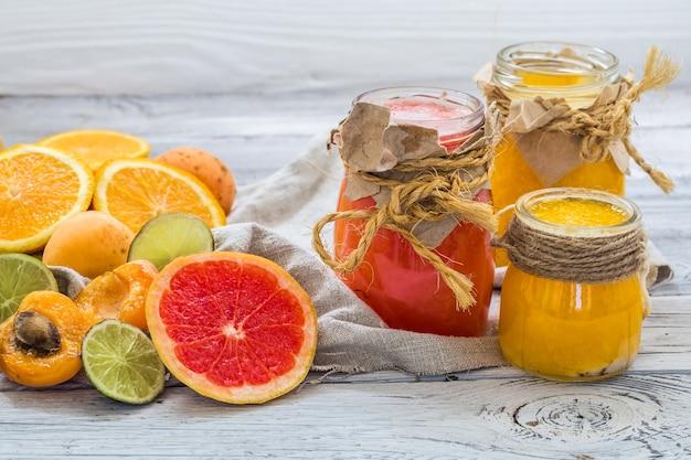 たくさんの新鮮な果物、木製の壁にカット、飲み物、健康食品