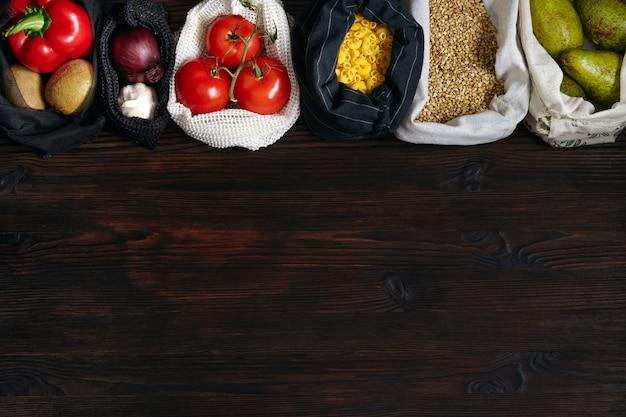 나무 테이블에 플라스틱 무료 및 친환경 가방에 신선한 유기농 식품이 많이 있습니다.