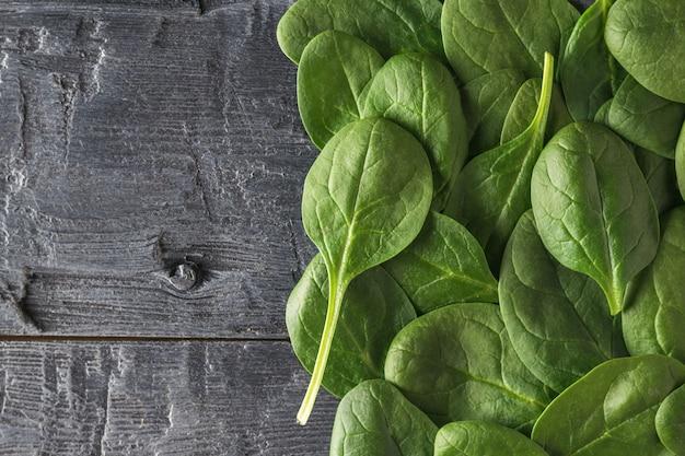 검은 나무 테이블에 신선한 시금치 잎이 많이 있습니다. 건강을 위한 음식. 채식주의 자 음식. 정상에서 본 모습.
