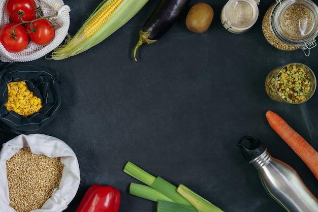 재사용 가능한 에코 백에 신선한 야채가 많고 칠판에 플라스틱 무료 은행에 유기농 식품이 많이 있습니다.