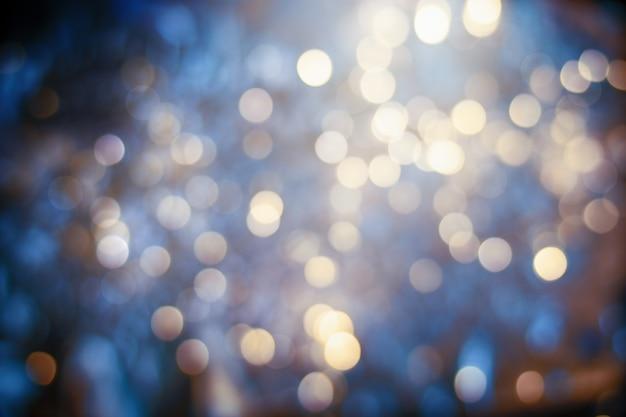 Много золотых размытых огней расфокусировки на синем фоне