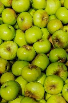 青リンゴがたくさん。自然からの健康とビタミン。閉じる。垂直。