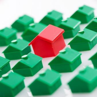 Много зеленых игрушечных домов и один красный