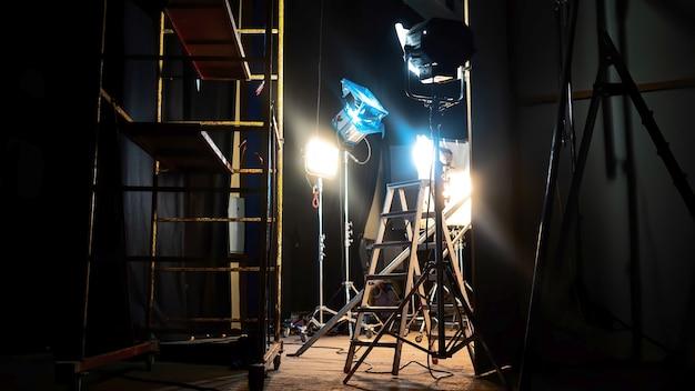 Много светодиодных систем освещения, несколько с цветными фильтрами и лестницами в съемочной площадке.