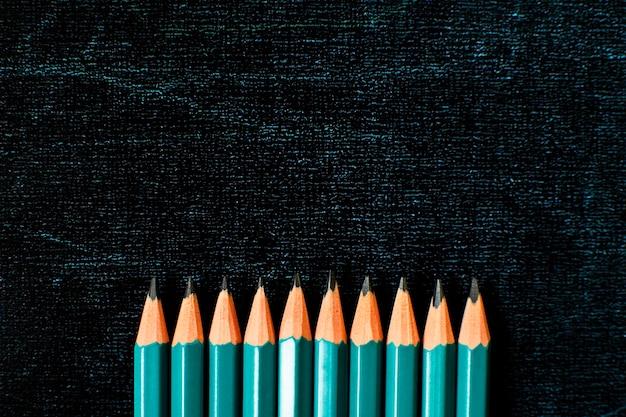 복사 공간이 있는 블랙 보드 배경에 연필이 많이 있습니다. 학교 개념으로 돌아가기. 플랫 레이.