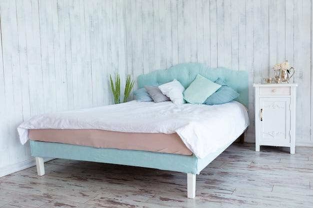 Много подушек в голубых тонах, выложенных на кровати