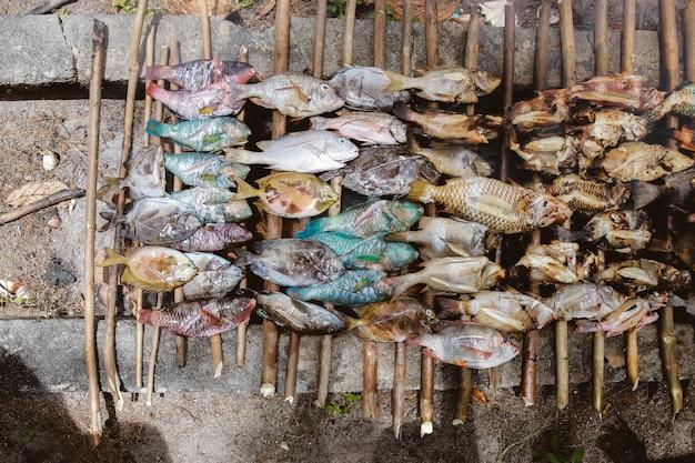 Много сырой рыбы, приготовленной на традиционном гриле