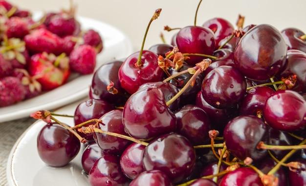 白いボウル、夏のベリーの収穫、食べ物の背景に熟したジューシーなチェリーがたくさん。