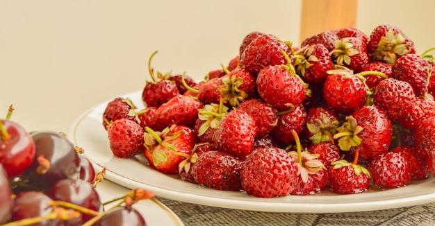 白いボウルに熟したジューシーなイチゴがたくさん、夏のベリーの収穫、食べ物の背景。