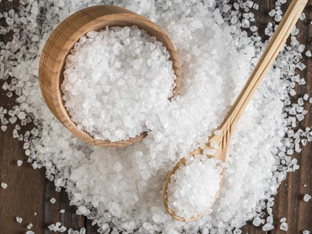 テーブルの上に木製のカップとスプーンで散らばった塩がたくさん。挽いた石の海塩。フラットレイ。