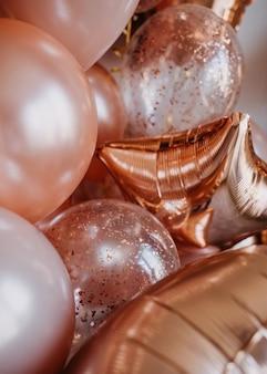 ヘリウムと光沢のあるピンクの風船がたくさん