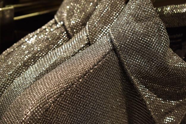 Много серебряных блесток на платьях на вешалках в магазине модная праздничная одежда на новый год и рождество.