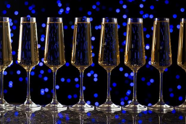 Множество бокалов для игристого вина на синих огней боке. популярный алкогольный напиток.