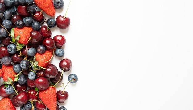 많은 딸기, 체리, 블루 베리. 흰색 테이블 배경 복사 공간에 달콤한 여름.