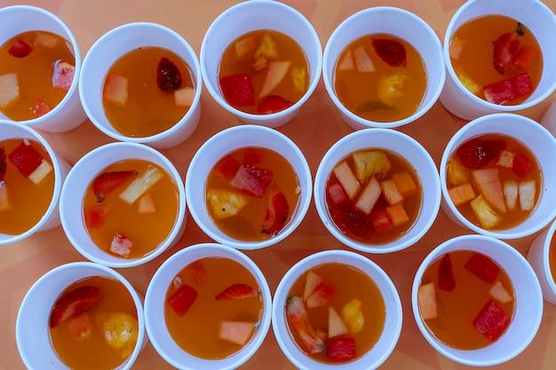하얀 컵에 빨간 딸기, 멜론, 파인애플로 만든 달콤한 과일 레모네이드가 많이 있습니다. 확대. 과일 조각에서 상쾌한 음료, 평면도