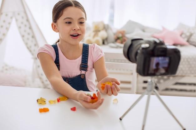 많은 과자. 사랑스러운 10 대 초반 소녀가 테이블에 앉아 카메라에 거미 곰 두 줌을 보여주고 시식하며 동영상 블로그를 촬영합니다.