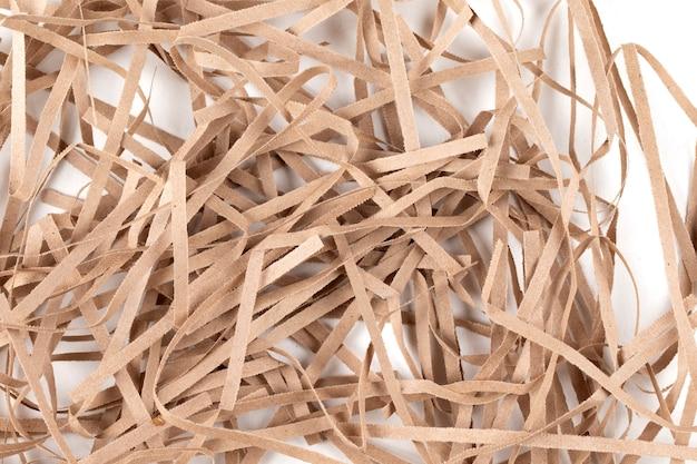 ベージュの紙の薄いストリップがたくさん。白い背景の上の贈り物のための装飾的な紙片
