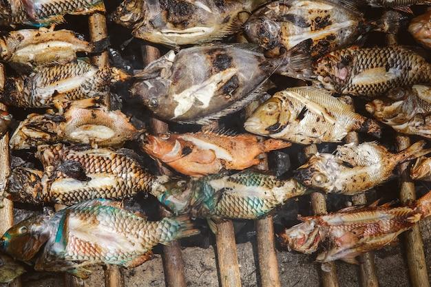 Много недоваренной рыбы, приготовленной на традиционном гриле