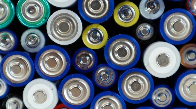 Много использованных бытовых щелочных батарей типа aa, aaa отправлено на переработку. переработка и проблемы экологии. вид сверху на фоне использованных батарей разных типов и размеров.