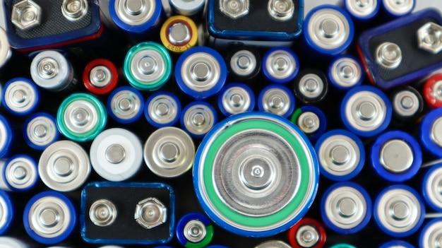 Много использованных бытовых щелочных батарей типа aa, aaa, pp3, d, c отправлено на переработку. переработка и проблемы экологии. вид сверху на фоне использованных батарей разных типов и размеров.
