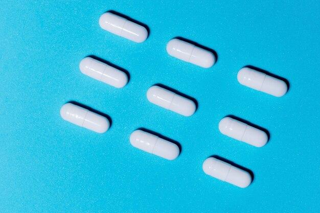 На синем столе много белых таблеток.