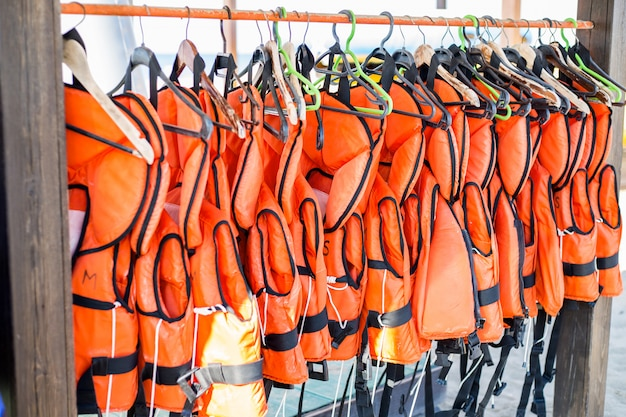 Lots of orange life jackets hanging on hangers.