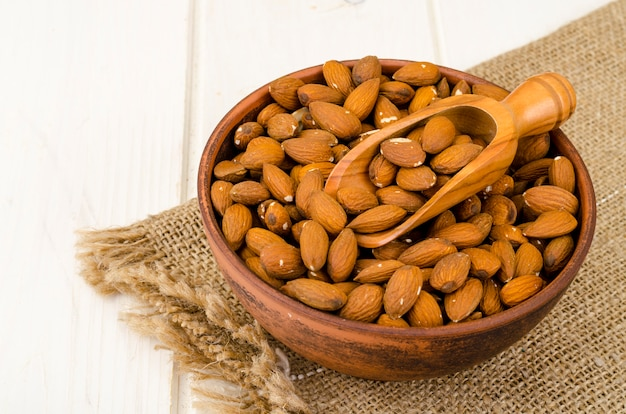 Lots peeled almonds in wooden bowl. photo