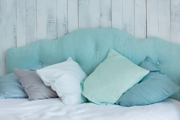 Lots of pillows in blue tones, laid out on a bed