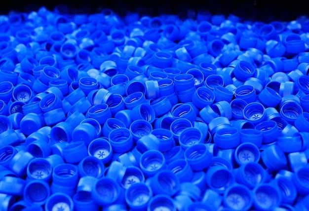 Lots of plastic blue pet bottle caps close up.